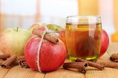 Ripe apples with with cinnamon sticks and glass of  apple drink  on  wooden table, on bright backgro