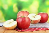 Ripe apples on  wooden table, on bright background