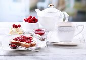 Fresh toast with  homemade butter and raspberry jam on plate on wooden table, on bright background