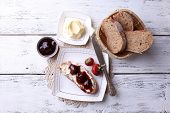Fresh toast with homemade butter and strawberry jam on light wooden background
