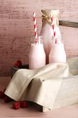 Bottles of tasty raspberry smoothie drinks on pink wooden background