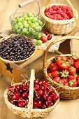 Fresh berries in baskets on wooden background