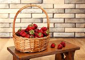 Fresh strawberries in basket on wall background