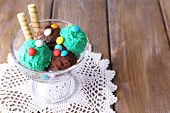 Chocolate ice cream with multicolor candies and wafer rolls in glass bowl, on wooden background