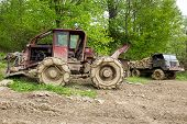 stock photo of logging truck  - Bulldozer and old truck loaded with logs in a forest - JPG