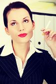 Beautiful business woman is holding cigarette, in office.