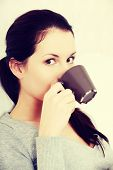 Beautiful woman is holding a cup of coffee. Indoor photo.