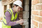 stock photo of insulator  - Architect Checking Insulation During House Construction project - JPG