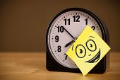 Drawn smiley face on a post-it note sticked on an alarm clock
