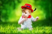 Happy Little Baby In Red Hat Having Fun In The Park On Solar Glade. Summer Vacations Concept. The Em