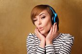 Pretty young woman with headphones listening to music with empty space