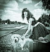 Beautiful woman with dog and suitcase on a train station. Black and white photo.