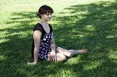 Young Caucasian Woman Sitting On Grass Shade