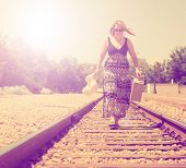 a girl walking down train tracks with a suitcase and hat done with a vintage retro like instagram fi