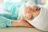Beautiful Muslim girl lying down with hijab and smiling