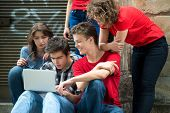 Group of teenagers with laptop computer outside