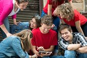 Group of cool teenagers playing with tablet