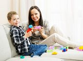 Happy young mother with her son on a sofa playing with building kit