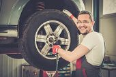 Cheerful serviceman unscrewing wheel in car workshop
