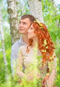 Portrait of cute cheerful couple hugging in the forest and looking in one side, happy wedding day, r