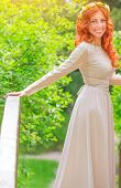 Beautiful happy bride wearing long beige dress and flower wreath in red hair, standing on little br