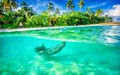 Active female swimming under water, enjoying beautiful sea nature, luxury beach resort on tropical i