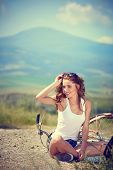 beautiful vintage girl sitting next to bike, summer time