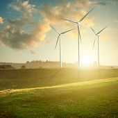 stock photo of wind wheel  - Wind generators turbines on sunset summer landscape - JPG