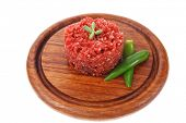 very big raw hamburger cutlet with sprouts and chilli pepper on wooden plate isolated over white bac