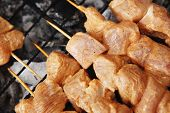 fresh raw chicken turkey shish kebab on skewers on grid over charcoal spread with sauce and coated w