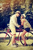 Happy young couple in summer park rides a bike. Romance and love.