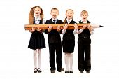 Cheerful schoolgirls and boys stand together and hold a huge pencil. Educational concept. Isolated o