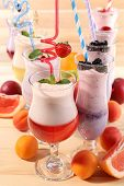 Delicious milkshakes on wooden table, close-up
