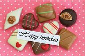 Happy Birthday card with selection of chocolates on pink background