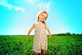 Pretty little girl on a meadow in summer day. Happy childhood. Blue sky.