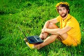 Handsome young man sitting on a grass with his laptop. Summer rest, vacation.