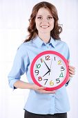 Young business woman with clock in room