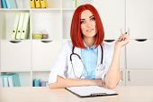 Young beautiful doctor with folder in cabinet