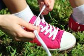 Young woman tying shoelace in park