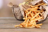 Tasty french fries and potato chips in metal baskets on wooden table, on light background