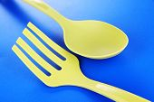 Plastic kitchen utensils on blue background