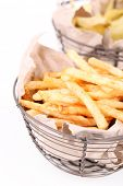 Tasty french fries in metal basket and potato chips, isolated on white