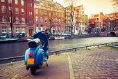 Blue Scooter Stands Parked On The Canal Coast In Amsterdam. Instagram Toned Effect