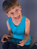 happy boy playing video games on the tablet computer