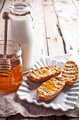 crackers, milk and honey on rustic wooden board