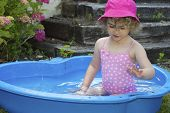 Young child having fun in a paddling pool.
