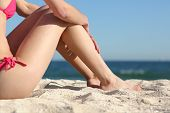 Sunbather Woman Legs Sitting On The Sand Of The Beach