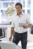 Happy young casual office worker holding tablet computer, smiling, looking at camera.