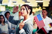 Patriotic businesswoman standing with USA flag in front of colleagues