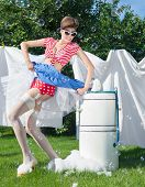 Skirt caught by wringer, pin up style photo of woman with vintage washing machine doing laundry outd